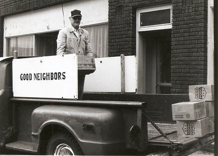 Black and white photo of man loading Good Neighbors truck with food