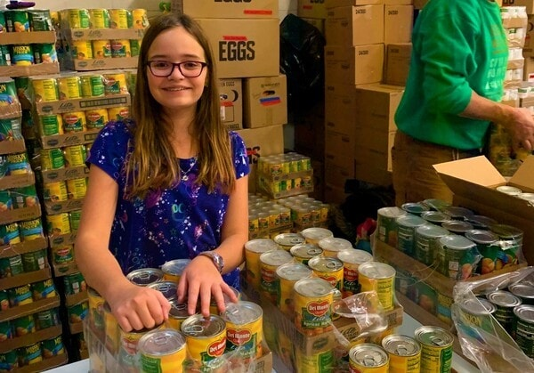 volunteer girl packing cans of food